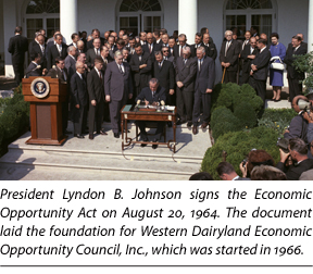 President Lyndon B. Johnson signs the Economic Opportunity Act of 1964
